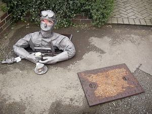 Scarecrow coming up out of a manhole