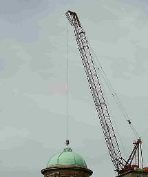 A crane's jib seems to be positioned that it is lifting a building
