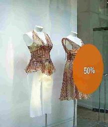 half dressed window dress dummy in shop window with 50 per cent reduction sign