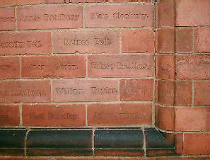 Brick wall with deceased names engraved on each brick