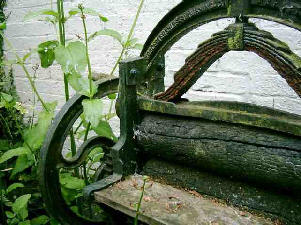 An old mangle rotting away with weeds growing in it