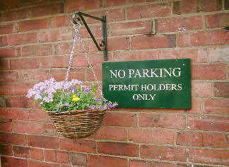 No parking sign with a large hanging basket of flowers