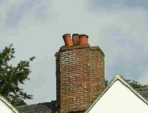 Three  chimney pots, one at an angle.
