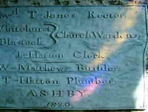 Old plaque in church partly illuminated by colours from a stained glass window