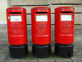 Three red pillar boxes standing together